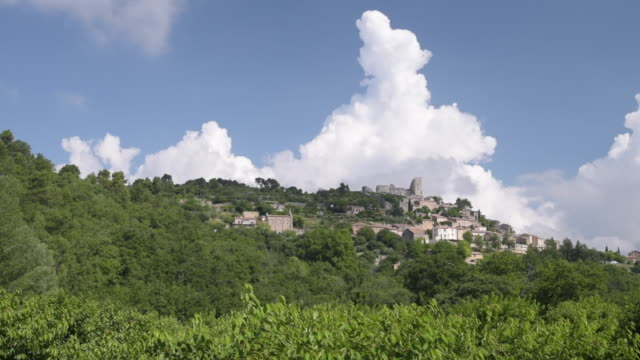 pan shot of mountain village lacoste with chateau de sade - luberon stock-videos und b-roll-filmmaterial