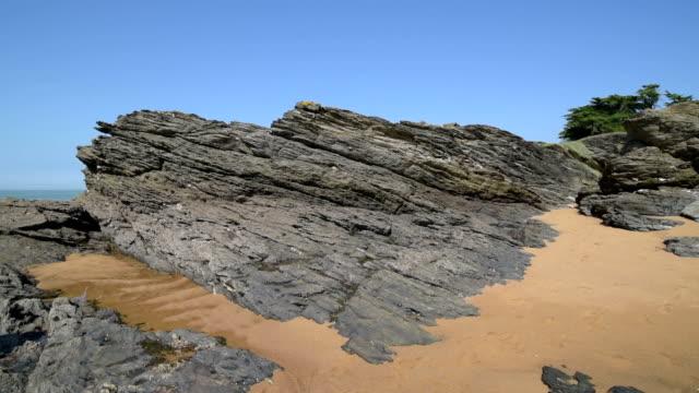 pan shot of rocky coast at cote de jade - 干潮点の映像素材/bロール