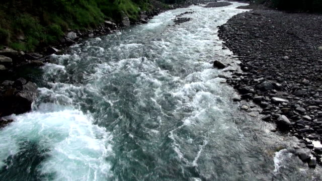 Pan shot of rushing river along valley floor in mountains.