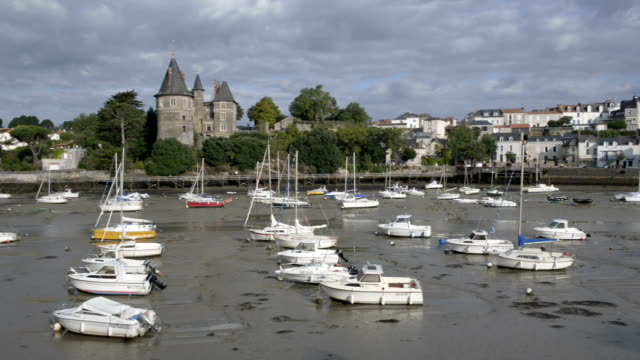 pan shot of sailing boats in port of pornic at low tide and the castle - low tide stock videos & royalty-free footage
