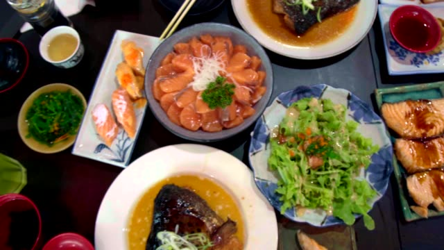 pan shot of salmon, salmon burns and roasted chicken japanese food on the table. top view of food. - roast dinner stock videos & royalty-free footage