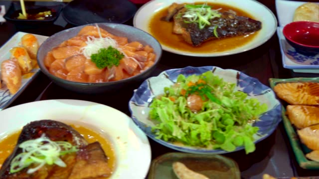 pan shot of salmon, salmon burns and roasted chicken japanese food on the table. top view of food. - table top shot stock videos & royalty-free footage