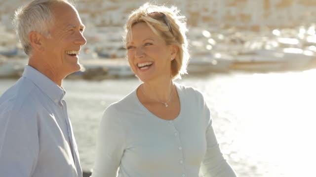 vídeos de stock, filmes e b-roll de pan shot of senior couple walking by marina in sunset - 50 54 anos