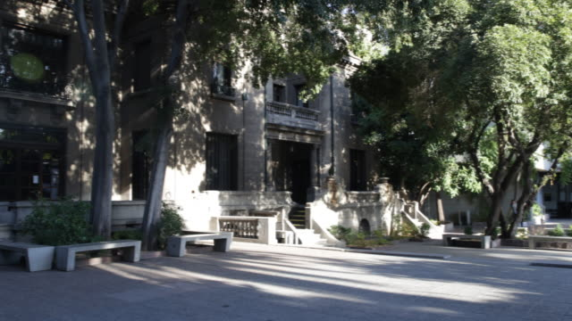 stockvideo's en b-roll-footage met pan shot of the sunny campus of the university alberto hurtado, in downtown santiago de chile, chile. students walking by. the university is named... - padre
