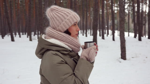 pan shot of toothy smiling woman gulping warm tea on a chilly winter day in the forest - mitten stock videos and b-roll footage