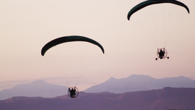 Pan shot of two powered paragliders at dusk.