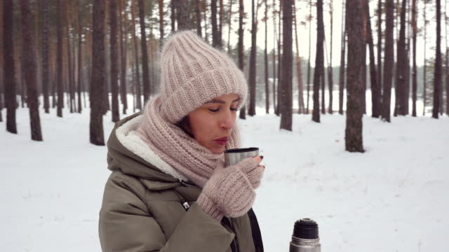 pan shot of woman drinking hot beverage and holding a thermos on a cold winter day in the forest - mitten stock videos and b-roll footage