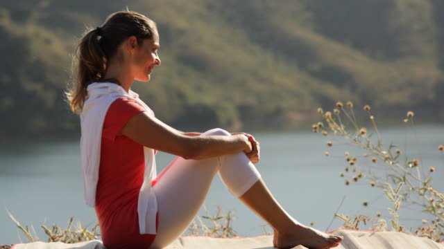 stockvideo's en b-roll-footage met pan shot of woman sitting by lake - alleen één oudere vrouw