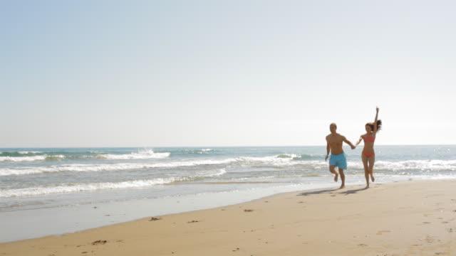 pan shot of young couple running on beach - 水泳パンツ点の映像素材/bロール
