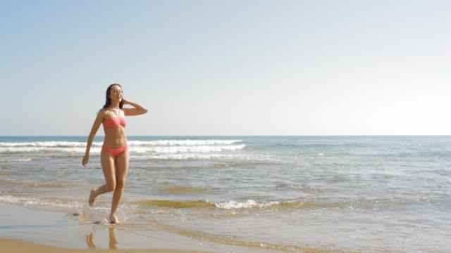 pan shot of young woman running on beach - スキップ点の映像素材/bロール