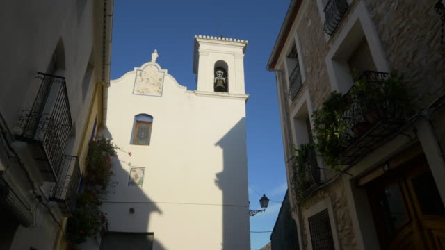 pan shot, old stone houses and balconies with church bell in narrow street