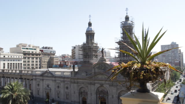 pan shot on a terrace with palms looking at the metropolitan cathedral and the commercial building next to the cathedral in santiago de chile - storia sociale video stock e b–roll