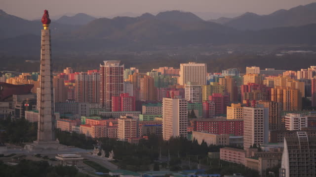 pan shot over pyongyang to juche tower with day to night time-lapse. north korea, drpk. - north korea stock videos & royalty-free footage