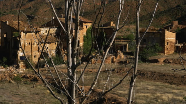 vidéos et rushes de pan shot past bare tree branches and cluster of derelict houses in hills of abandoned village el campo, aragon - bare tree