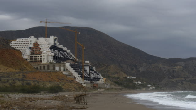 pan shot, tidal waves in front of abandoned Hotel Algarrobico and construction site at Cabo de Gata