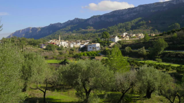pan shot, white houses and church steeple of small village Benissivà with hills