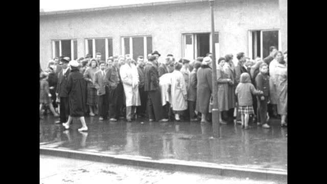 pan showing refugees from east berlin queuing outside a relief centre kitchen in west berlin; 1959. - 1950 1959 stock videos & royalty-free footage