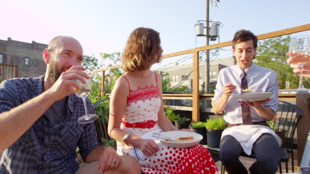 ms pan smiling group of friends sitting together sharing dinner and wine in rooftop garden on summer evening - シャツとネクタイ点の映像素材/bロール