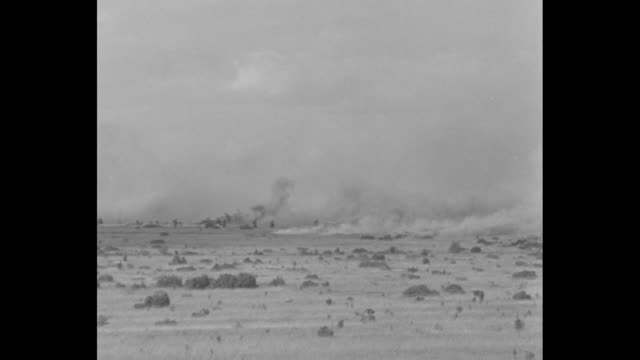 vidéos et rushes de ws pan smokescreen on field during french military maneuvers / french soldiers move along gravel road as smokescreen goes up in background / soldiers... - manoeuvre militaire