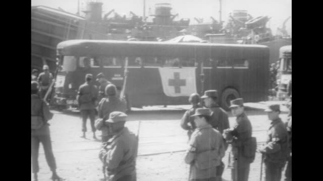 pan south korean and un troops stand near line of ambulances with ships in background continue pan to exit of lst with 1090 labeled above door / side... - insignia stock videos and b-roll footage