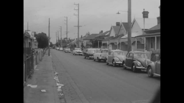 pan suburban street row of mostly VW Beetle cars parked on street with weatherboard houses vs small bungalow house with metal rubbish bin out the...