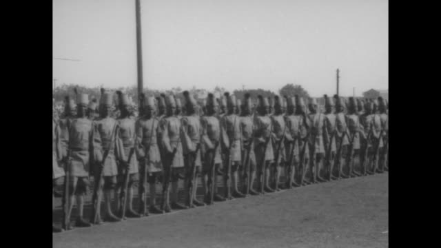 pan sudanese adults and children gathered under festive poles and ribbons for arrival of british high commissioner for egypt lord george lloyd guards... - colonial stock-videos und b-roll-filmmaterial