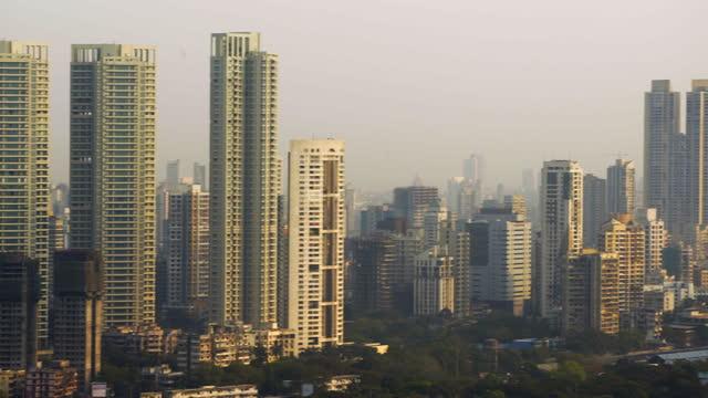 vídeos de stock e filmes b-roll de pan: sunlit skyscrapers in striking cityscape on sunny day - mumbai, india - panning
