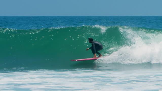 pan: surfer catching a barrel (shot on red) - malibu stock-videos und b-roll-filmmaterial