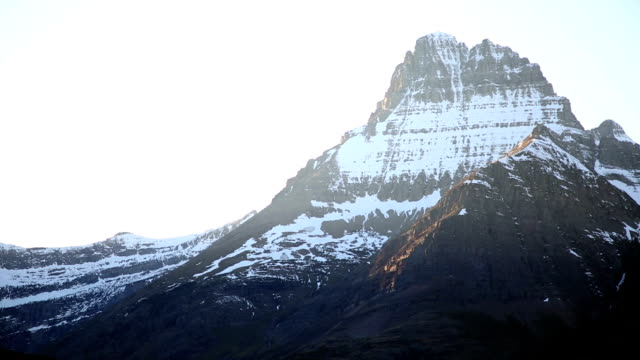 Pan telephoto shot of snow covered mountain peak at sunset.
