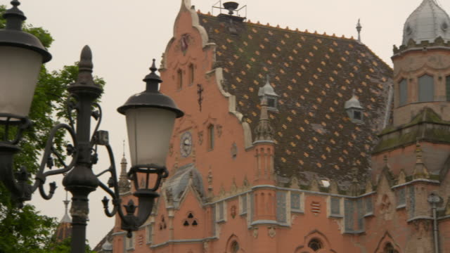 vidéos et rushes de pan: the exquisite, intricate roof and tiling of city hall in kecskemet - roche