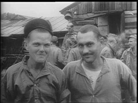 Pan through Ofuna POW camp Allied prisoners of the Japanese smile happily at the camera eat rations / soldier spits out a bite of rice and throws the...