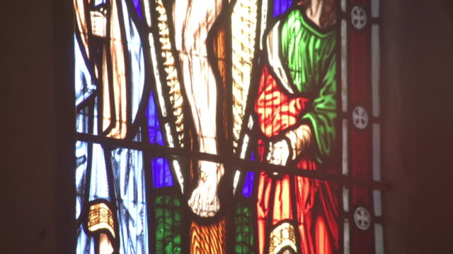 Pan through tilt of Jesus on the cross in a stained glass window