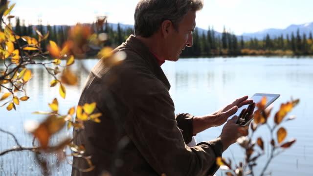 Pan thru foliage to man using digital tablet, mountain lake