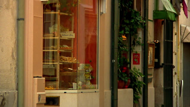pan tilt down young girl running out of bakery (boulangerie) carrying baguettes / provence, france - french bakery stock videos & royalty-free footage