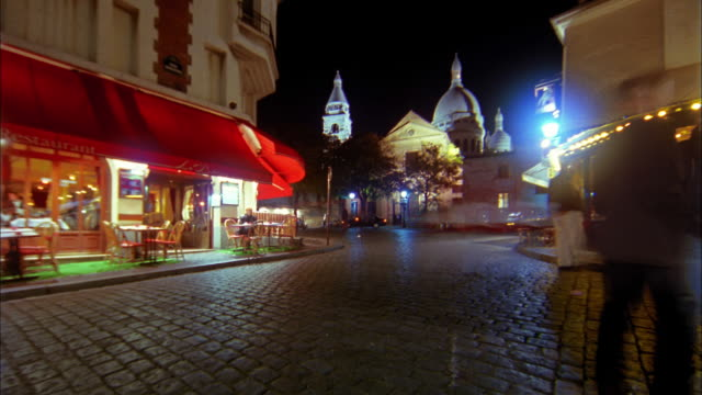 pan time lapse crowds in montmartre at night w/sacre coeur in background / paris, france - basilique du sacre coeur montmartre stock videos & royalty-free footage