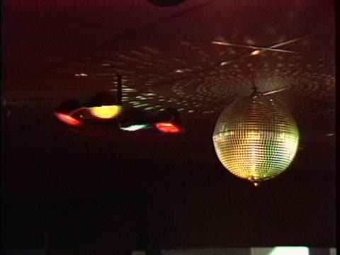 pan to a disco ball and multi-colored lights spinning on a ceiling at studio 54 in 1978. - spinning stock videos & royalty-free footage