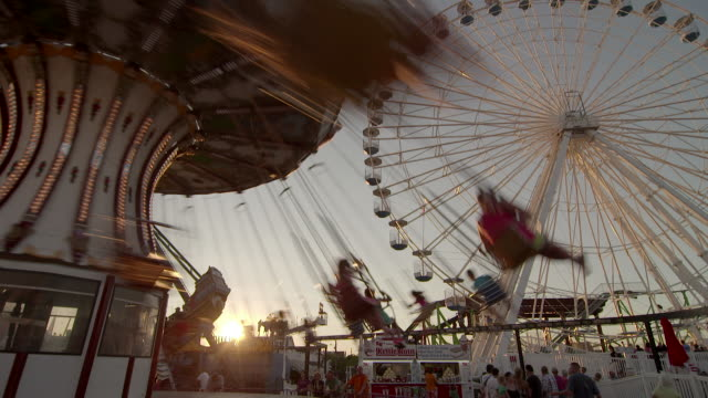 Pan to an amusement park swing as it twirls in the sunset as a Ferris wheel rotates behind.  Families are having fun at a resort town on the Jersey Shore