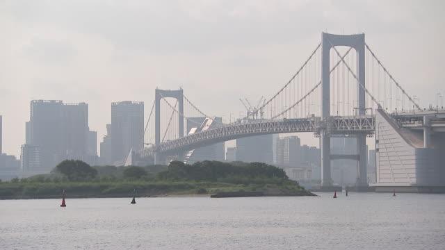 pan to an establishing shot of the rainbow bridge in tokyo, japan. - tokyo bay stock videos & royalty-free footage