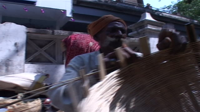 vídeos de stock e filmes b-roll de pan to an indian man sitting on a street weaving a basket rush weaving is an ancient craft in india weavers use pliable grasses and rushes with which... - palha de milho
