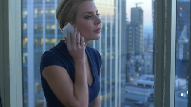 pan to businesswoman using mobile phone in high level corporate office building - swiss re stock videos & royalty-free footage