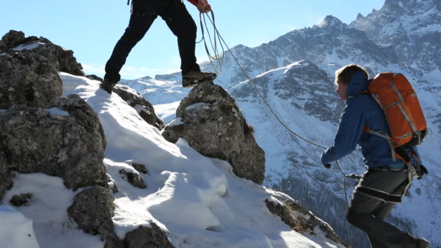 pan to father belaying son on snowy ridge, mountains behind - belaying stock videos & royalty-free footage