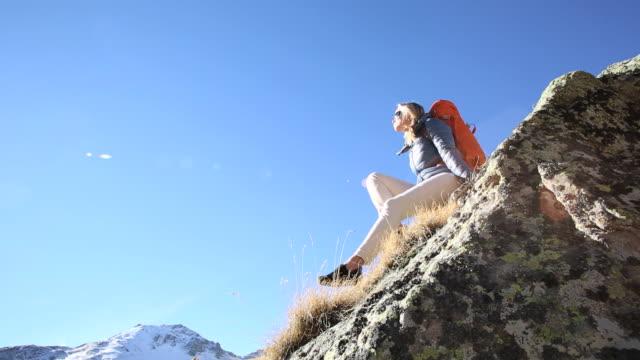 vídeos de stock, filmes e b-roll de pan to female hiker relaxing on rock ridge, alpine meadow - só uma mulher de idade mediana