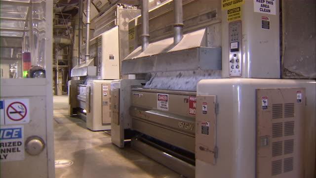 pan to machines processing cotton on factory floor. - 禁煙マーク点の映像素材/bロール