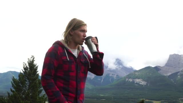 Pan to man enjoying hot drink on mountain ridge