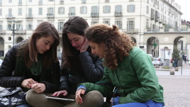 pan to teen  girls looking at digital tablet, in urban piazza - only teenage girls stock videos and b-roll footage