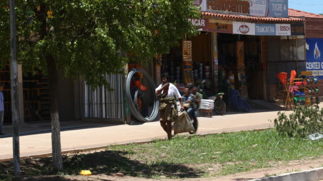 a pan to the left is showing a poor man who is carrying his bag and is walking on the center stripe of a main road with a shop near ascension and the... - america del sud video stock e b–roll