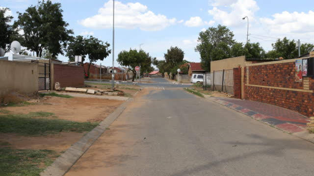 a pan to the left showing a side street in orlando west soweto a township of johannesburg where nelson mandela lived before his imprisonment - 社会史点の映像素材/bロール