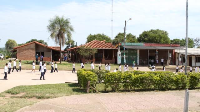 stockvideo's en b-roll-footage met pan to the left, showing school children marching up in front of the mayor's office in el puente, bolivia - puente