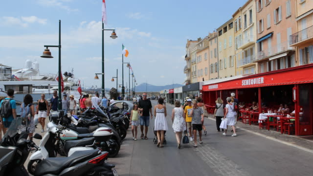 A pan to the left showing the front terrace of a cafe overlooking the promenade Tourists are passing by