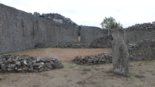 vídeos de stock, filmes e b-roll de a pan to the left showing the ruins of an ancient city complex site in the southeastern hills of zimbabwe which used to be the capital of the kingdom... - ruína antiga